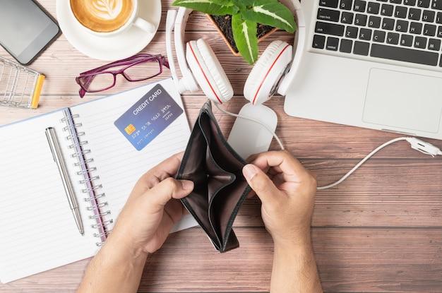 Um homem abre carteira sem dinheiro na mesa que consiste em cartões de crédito no notebook Foto Premium