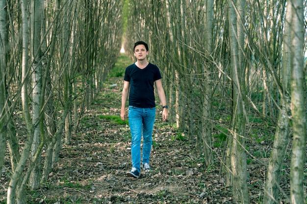 Um homem afinado positivamente em uma caminhada na floresta experimenta uma sensação de sucesso Foto Premium