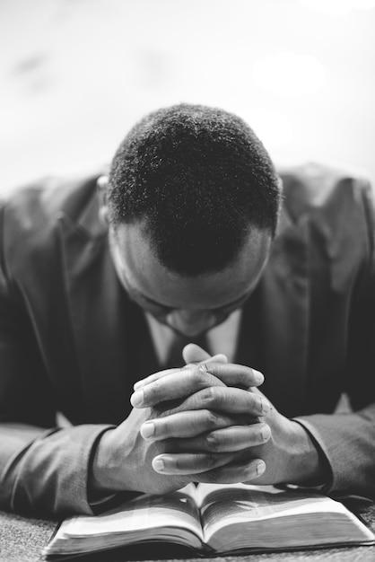 Um homem afro-americano solitário orando com as mãos na bíblia e a cabeça baixa Foto gratuita