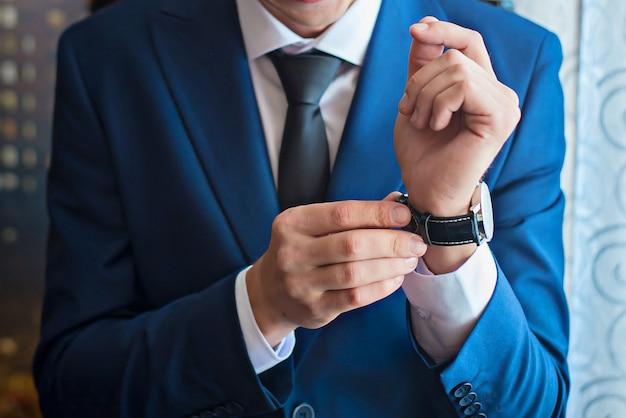 Um homem ajusta o relógio na mão closeup Foto Premium