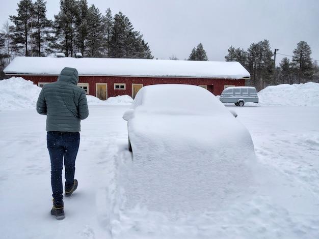 Um homem andando ao lado de um carro coberto de neve Foto Premium
