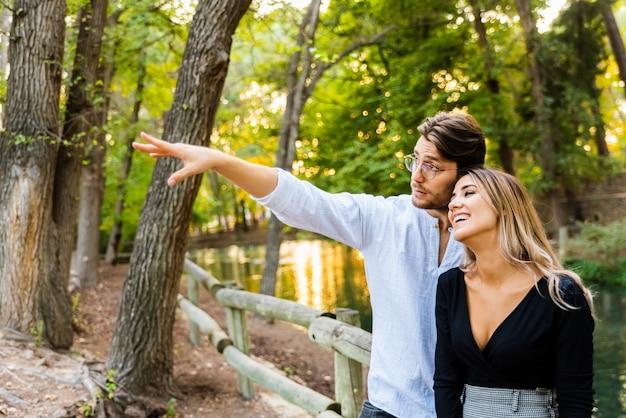 Um homem aponta o dedo para o lado enquanto abraça a namorada que o olha apaixonada. Foto Premium