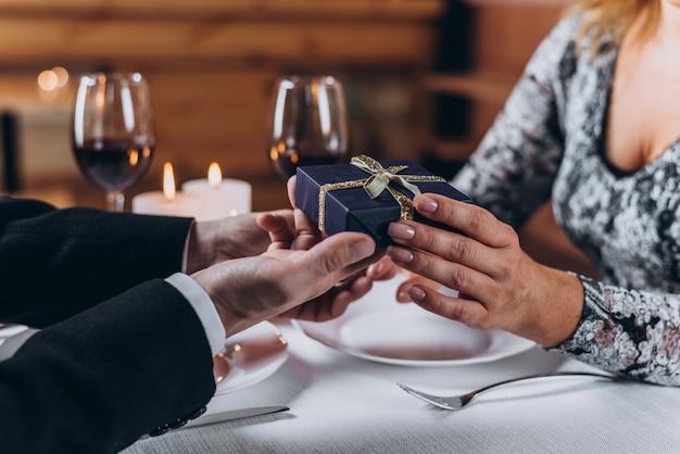 Um homem apresenta um presente para uma mulher no jantar Foto Premium
