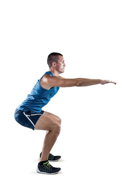 Um homem apto fazendo agachamentos Foto Premium