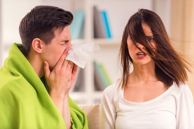 Um homem assoa o nariz em um guardanapo, enquanto uma garota se senta nas proximidades. Foto Premium