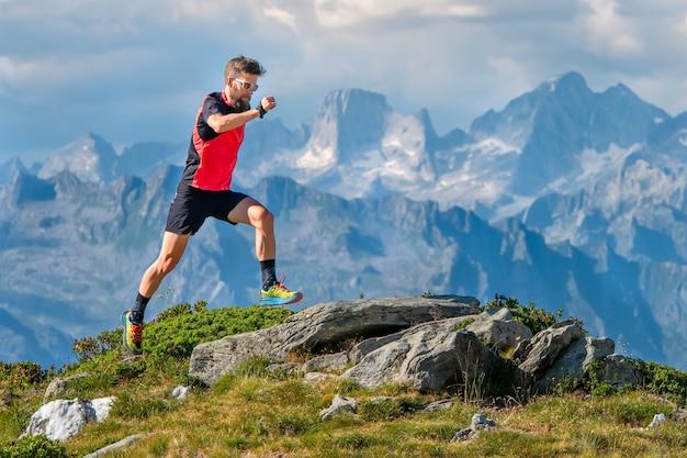 Um homem atleta skyrunner treina nas montanhas altas Foto Premium