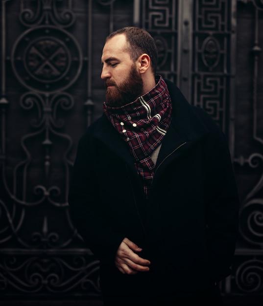 Um homem barbudo brutal bonito em uma jaqueta e cachecol fica perto de um portão de metal Foto Premium