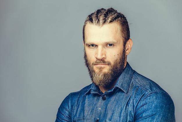 Um homem barbudo em roupas casuais está apontando para fora, sorrindo, Foto Premium