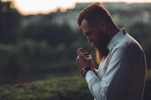Um homem barbudo está fumando um cigarro contra o pôr do sol Foto Premium