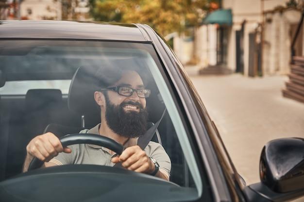 Um homem barbudo moderno dirigindo um carro Foto gratuita