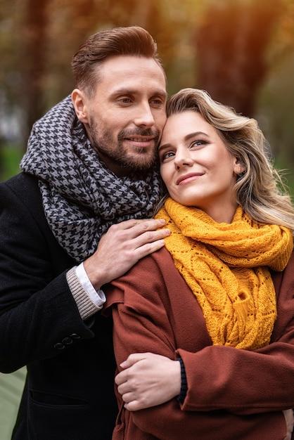 Um homem bonito e uma mulher se abraçam por trás e sorriem se olhando no parque de outono Foto Premium
