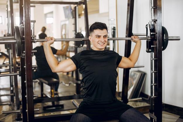Um homem bonito está envolvido em um ginásio Foto gratuita