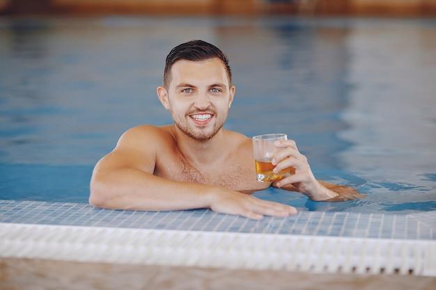 Um homem bonito flutuando em uma grande piscina em casa e bebendo uísque Foto gratuita