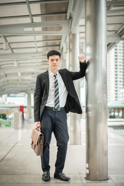 Um homem bonito, vestindo terno preto e camisa branca, está segurando uma bolsa e parado na cidade. Foto Premium