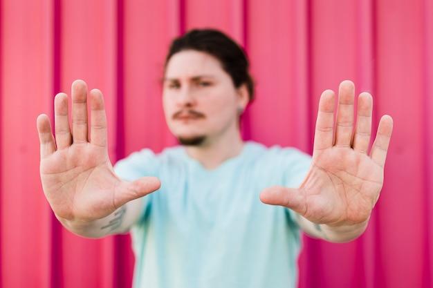 Um homem bravo, fazendo o gesto de parada contra o pano de fundo vermelho Foto gratuita