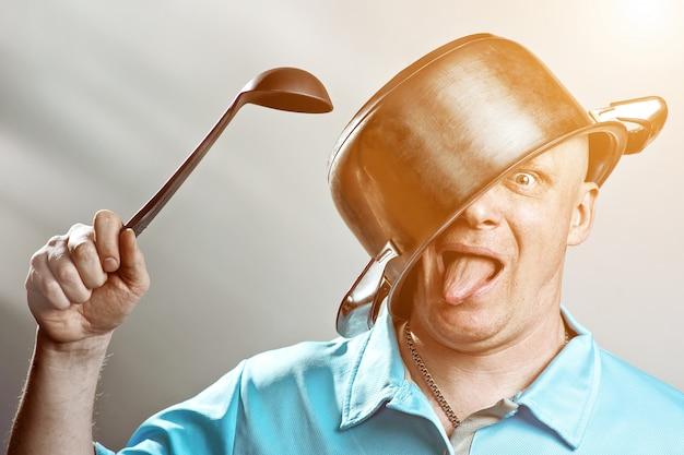 Um homem brutal careca de camiseta azul colocou um pote na cabeça Foto Premium