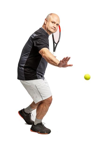 Um homem careca de meia-idade joga tênis. canhoto. isolado em um fundo branco Foto Premium