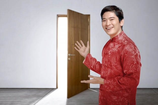Um homem chinês asiático vestido cheongsam convida para a casa para comemorar o ano novo chinês Foto Premium
