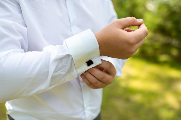 Um homem coloca uma camisa cara com abotoaduras pela manhã. Foto Premium