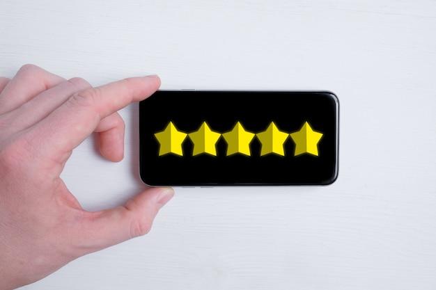 Um homem coloca uma classificação abstrata de cinco estrelas em um smartphone em um branco. melhor pontuação. postura plana. Foto Premium