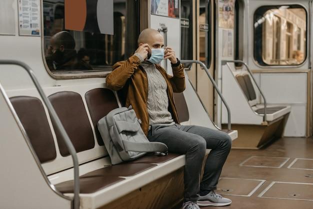 Um homem com barba está colocando uma máscara médica no rosto para evitar a propagação do coronavírus em um vagão do metrô. um cara careca com uma máscara cirúrgica contra covid-19 está sentado em um trem do metrô. Foto Premium