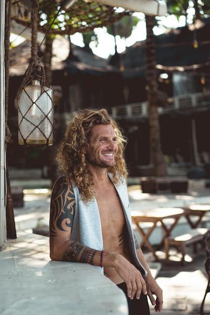 Um homem com cabelo longo encaracolado em um local de pesca. pescador no oceano Foto gratuita