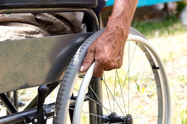 Um homem com deficiência está sentado em uma cadeira de rodas Foto Premium