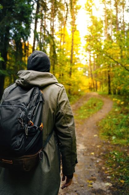 Um homem com mochila caminha na incrível floresta de outono. Foto Premium