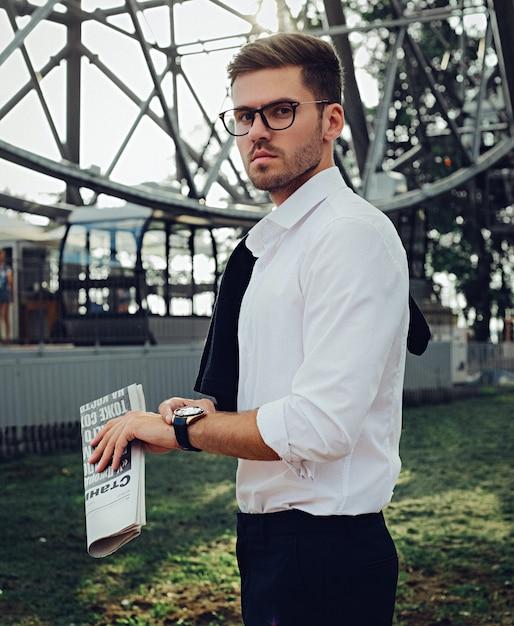 Um homem com roupas clássicas e óculos segurando um jornal Foto Premium
