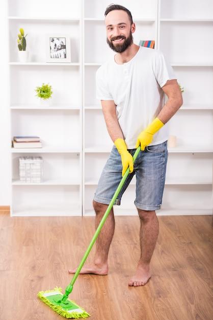 Um homem com um esfregão lava pisos em casa e sorri. Foto Premium