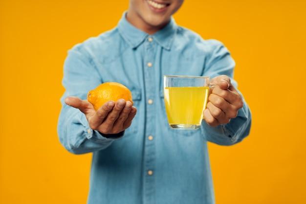 Um homem com um limão nas mãos e um copo com um remédio para beber Foto Premium
