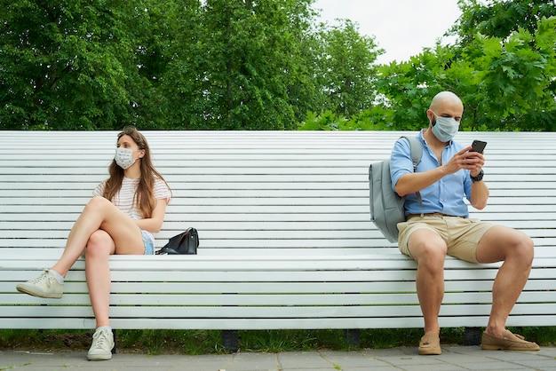 Um homem com um telefone e uma mulher sentados em extremos opostos do banco, mantendo distância um do outro para evitar a propagação do coronavírus. Foto Premium