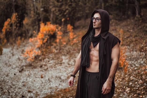 Um homem com um torso nu fica na floresta de outono Foto Premium