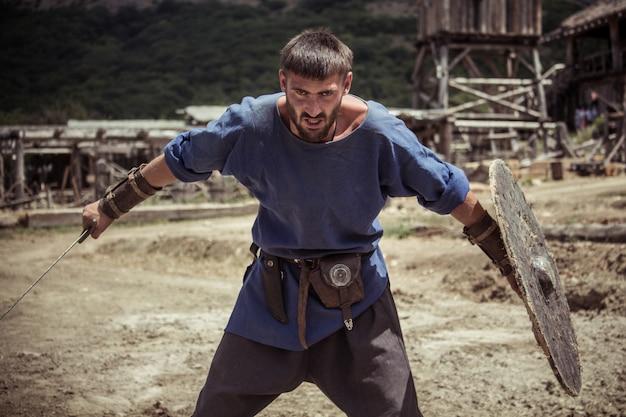 Um homem com um traje viking segura uma espada e um escudo Foto Premium