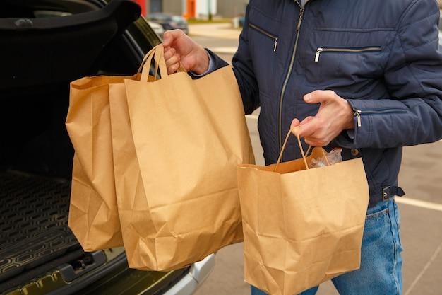 Um homem com uma máscara protetora no rosto coloca pacotes de comida no carro Foto Premium