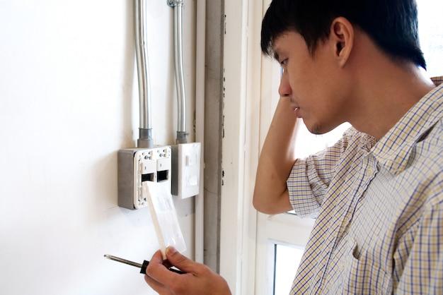 Um homem confuso para consertar o interruptor elétrico na parede. Foto Premium