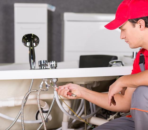 Um homem conserta uma pia quebrada em casa. Foto Premium