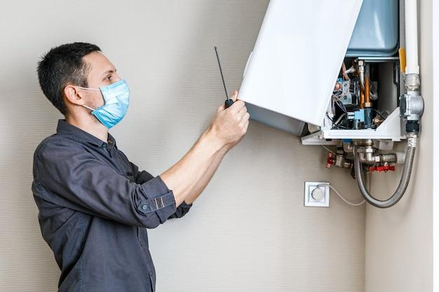 Um homem consertando uma caldeira com uma máscara médica Foto Premium