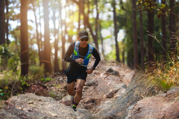 Um homem corredor de trilha. e pés de atleta usando sapatos esportivos para trilha correndo na floresta Foto Premium