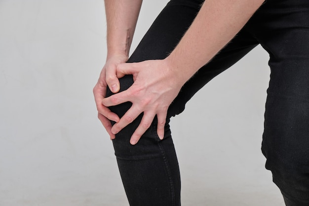 Um homem coxo de jeans massageia o joelho. conceito de dor na perna. Foto Premium