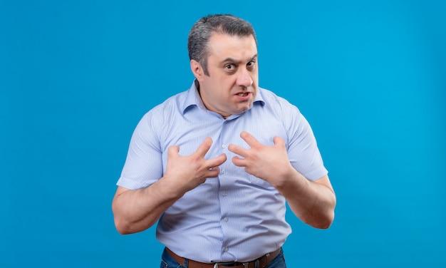 Um homem de camisa azul mostra emocionalmente agressão e raiva com as mãos apontando para si mesmo em um espaço azul Foto gratuita