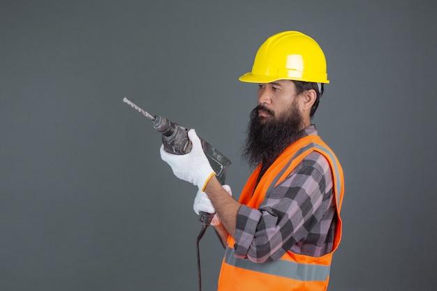 Um homem de engenharia usando um capacete amarelo com equipamentos de construção em um cinza. Foto gratuita
