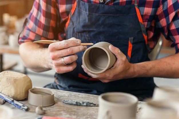Um homem de meia idade em um trabalho uniforme de pilha de madeira com uma forma de xícara de barro em uma grande manufatura de cerâmica criativa. Foto Premium