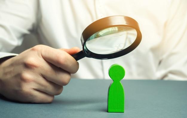 Um homem de negócios está segurando uma lupa sobre uma figura do homem verde. procure um funcionário talentoso. Foto Premium