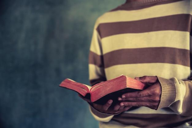 Um homem de pé durante a leitura da bíblia ou livro sobre a parede de concreto com luz de janela Foto gratuita