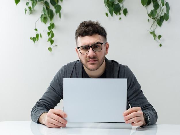 Um homem de vista frontal jovem de casaco cinza na mesa branca Foto gratuita