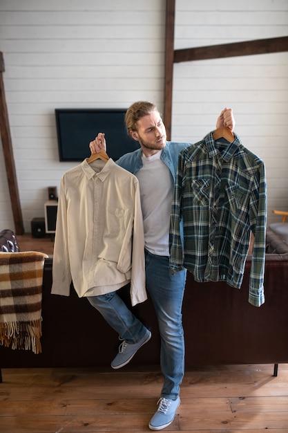 Um homem decidindo qual camisa vestir Foto Premium