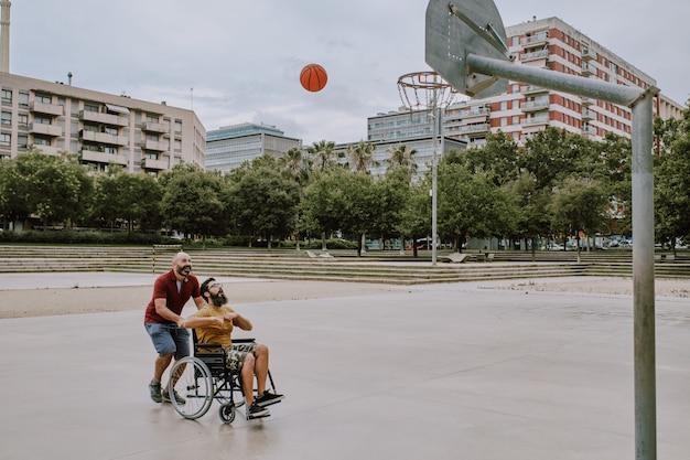 Um homem deficiente em cadeira de rodas joga cesta com um amigo Foto Premium
