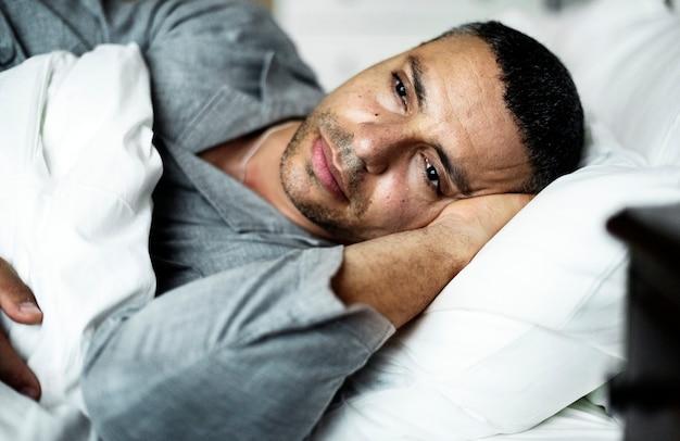 Um homem deitou-se na cama Foto Premium