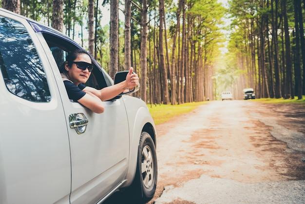 Um homem dirigindo uma caminhonete por caminhos irregulares que é um caminho no meio da floresta de pinheiros Foto Premium
